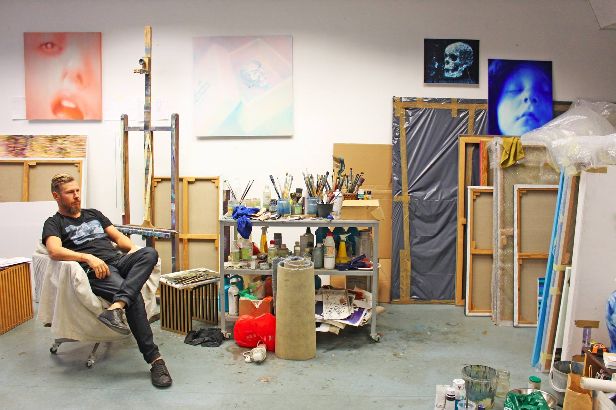 Ritums relaxing in his studio wearing the Tshirt in support of the future art museum